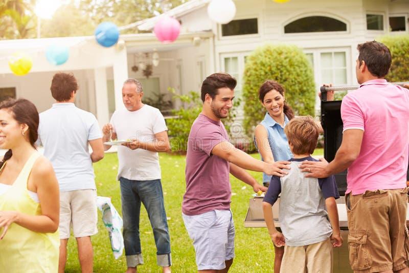 Multi família da geração que aprecia o partido no jardim junto imagens de stock