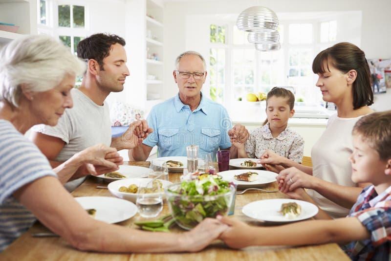 Multi família da geração que reza antes da refeição em casa foto de stock