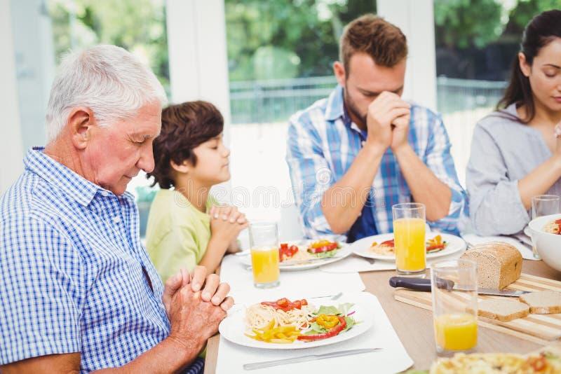 Multi família da geração que reza ao sentar-se na mesa de jantar imagens de stock royalty free
