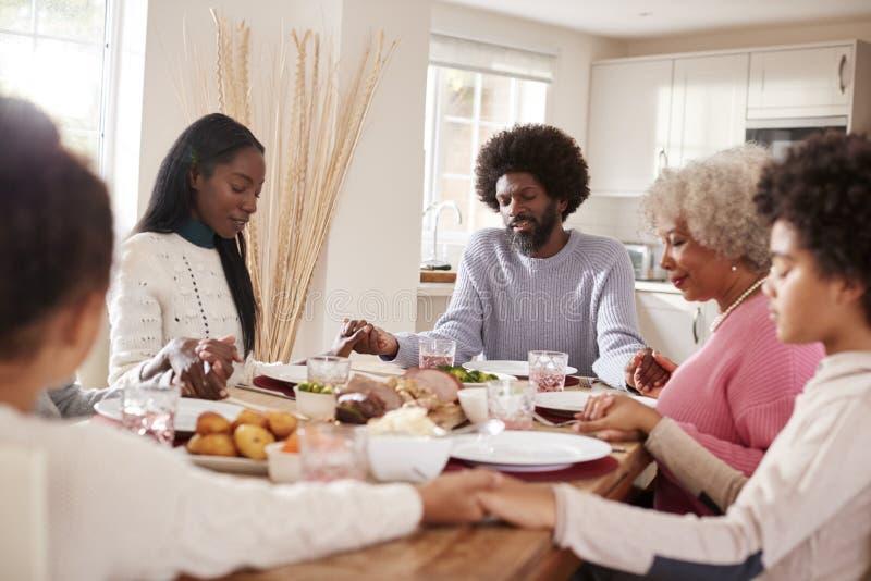 Multi família da raça misturada da geração que guarda as mãos e que diz a benevolência antes de comer seu jantar de domingo foto de stock