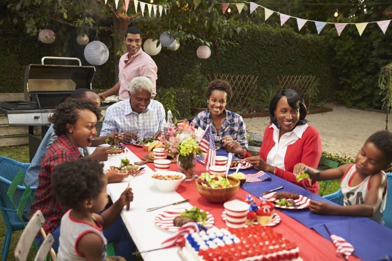 Multi famiglia del nero della generazione alla tavola per il barbecue del 4 luglio immagine stock libera da diritti