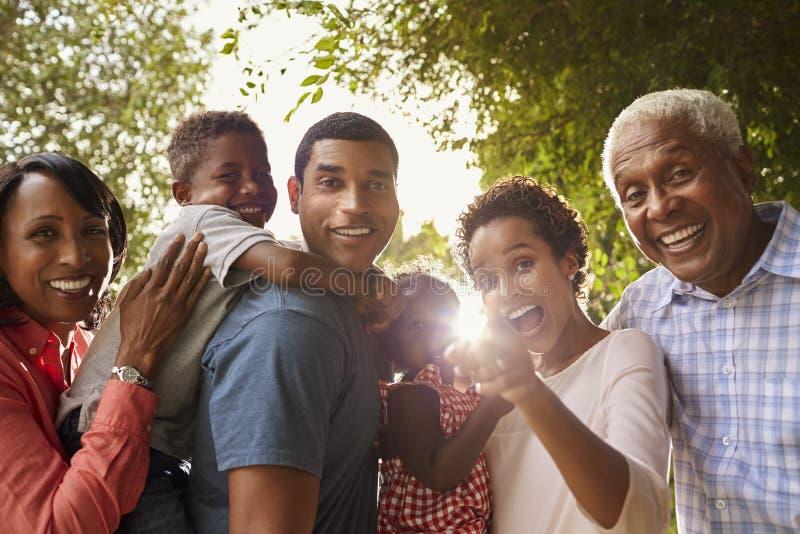Multi famiglia del nero della generazione nello sguardo del giardino alla macchina fotografica fotografie stock libere da diritti