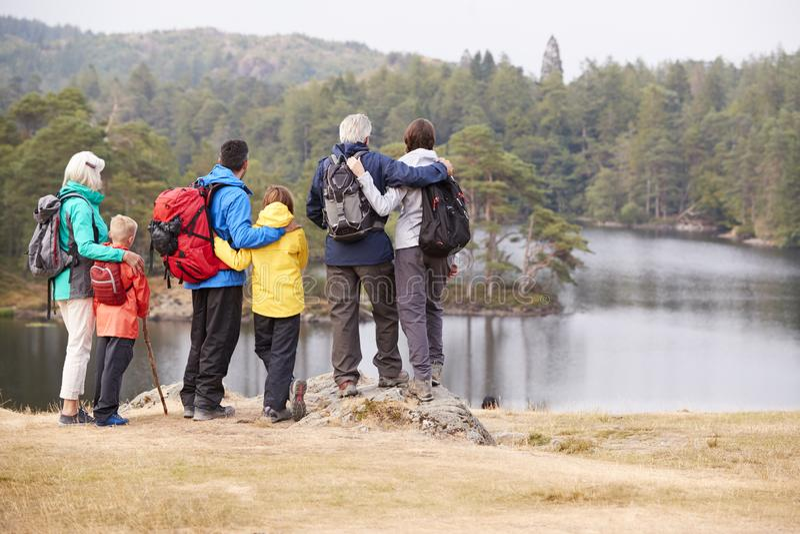 Multi famiglia della generazione che abbraccia e che ammira la vista della riva del lago, vista posteriore, distretto del lago, R fotografie stock