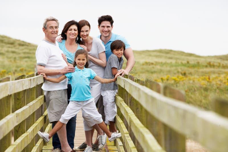 Multi famiglia della generazione che cammina lungo il ponte di legno immagine stock libera da diritti