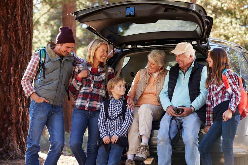 Multi famiglia della generazione che fa una pausa un'automobile prima dell'aumento della foresta fotografia stock