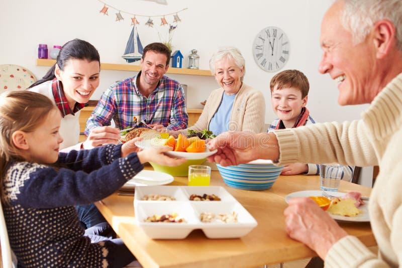 Multi famiglia della generazione che mangia pranzo al tavolo da cucina fotografia stock libera da diritti