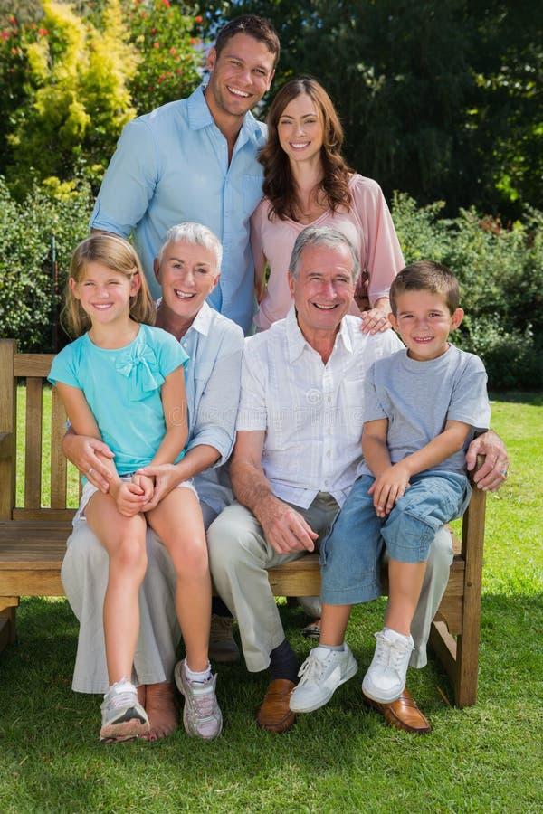 Multi famiglia felice della generazione che si siede nel parco immagine stock