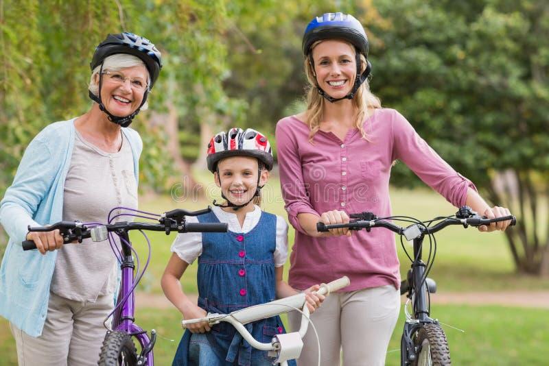 Multi famiglia felice della generazione sulla loro bici al parco immagine stock libera da diritti