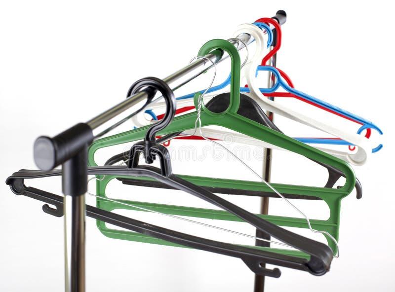 Multi farbige Kleiderbügel auf Metallquerlatte über Weiß lizenzfreie stockfotos