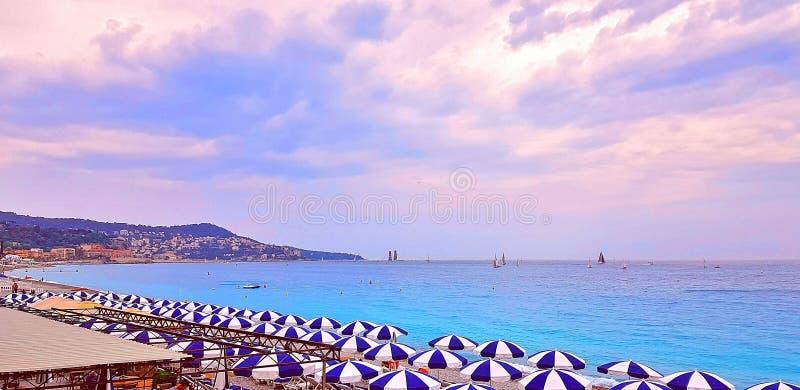 Multi farbige Regenschirme auf dem Strand in Nizza- und Türkisruhigem Wasser auf dem Taubenschlag d ` Azur, Frankreich Sonnenunte lizenzfreies stockfoto
