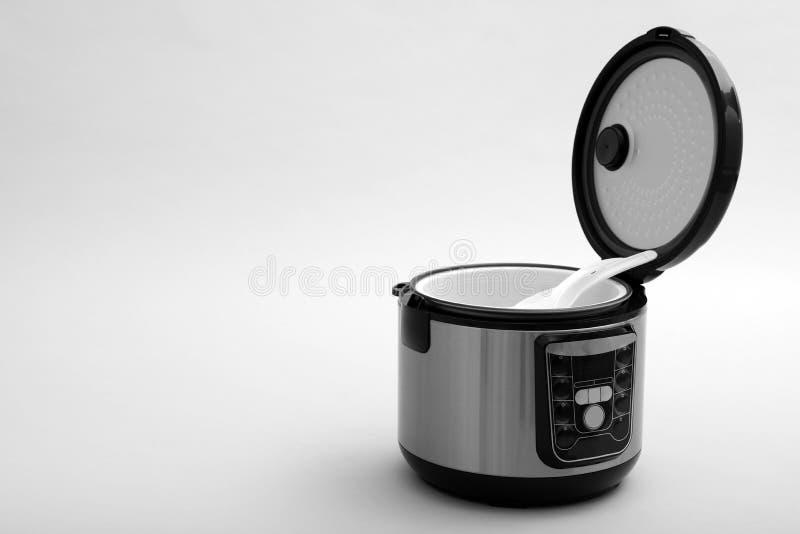 Multi fornello elettrico moderno con il cucchiaio e la siviera su fondo grigio immagini stock libere da diritti