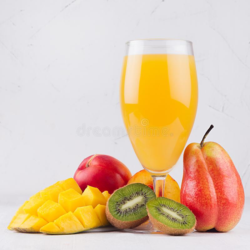 Multi fruit tropical juice in elegant glass with different fruits on white wood board, square. royalty free stock photography