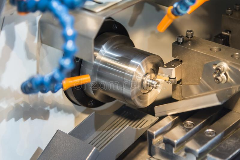 Multi function CNC lathe machine cutting the small part. Hi technology manufacturing stock photography