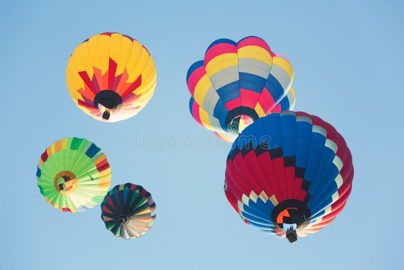Multi gekleurde hete luchtballons in zonnige blauwe hemel royalty-vrije stock foto's