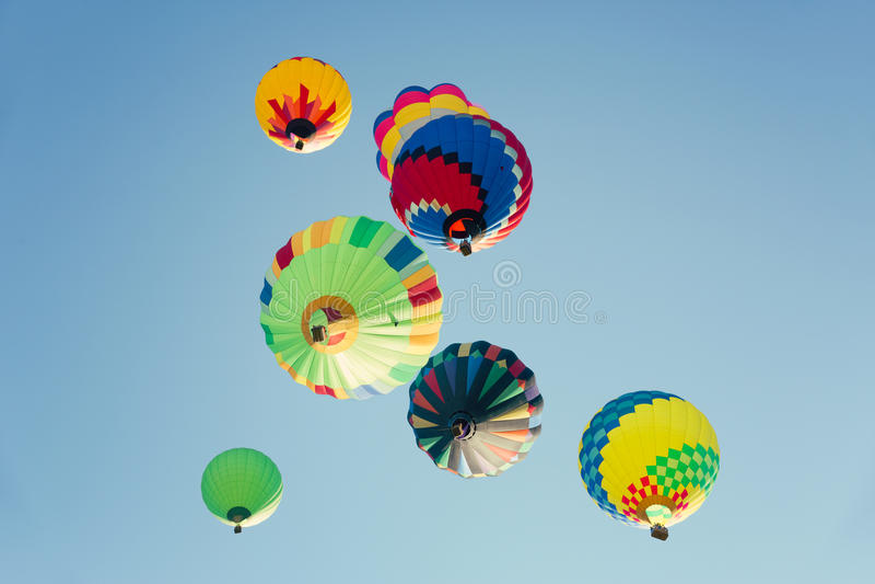 Multi gekleurde hete luchtballons in zonnige blauwe hemel stock foto's