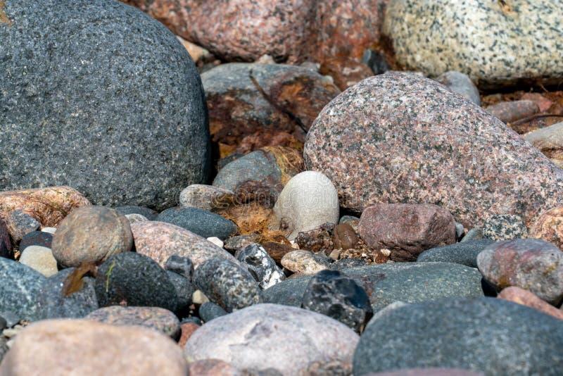 Multi gekleurde kiezelstenen op een strand stock foto's