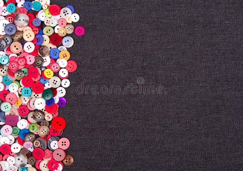 Multi gekleurde knopen op denim stock foto