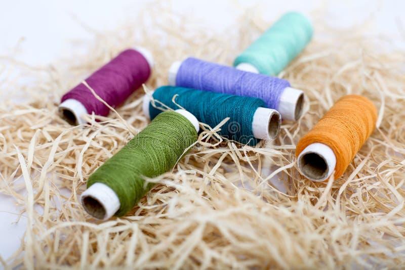 Multi Gekleurde naaiende draad op het rafigras stock foto's