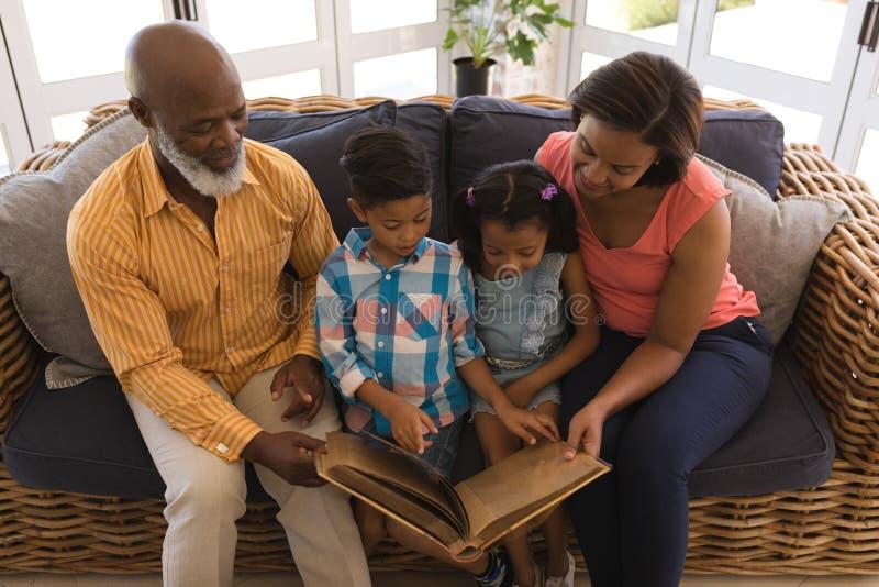 Multi-generation οικογένεια που διαβάζει ένα βιβλίο ιστορίας στο καθιστικό στοκ εικόνες με δικαίωμα ελεύθερης χρήσης
