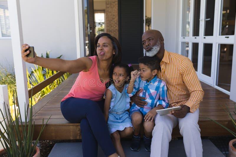 Multi-generation οικογένεια που παίρνει selfie με το κινητό τηλέφωνο στο μέρος στοκ φωτογραφία