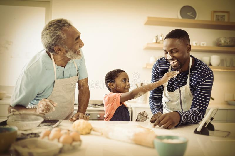 Multi-generation οικογένεια με το αλεύρι στη μύτη που στέκεται στην κουζίνα στοκ φωτογραφίες