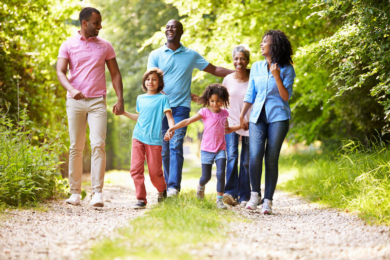 Multi Generation African American Family On Country Walk. Looking At Each Other Smiling Whilst Holding Hands stock images