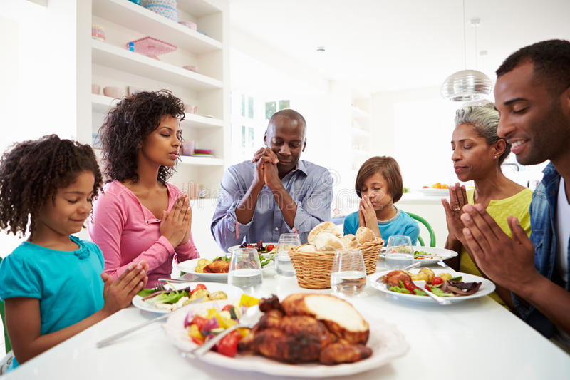 Multi Generation African American Family Praying At Home. In Kitchen With Eyes Closed stock images