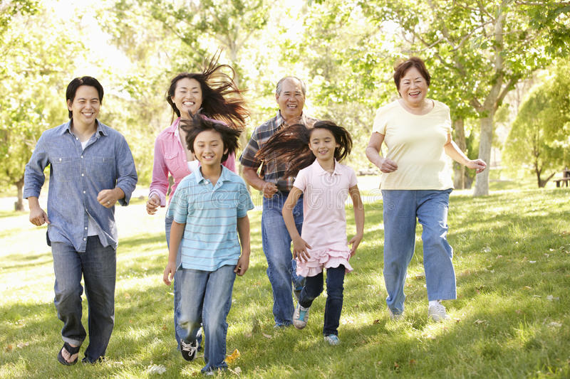 Multi-generation Asian family running in park stock images