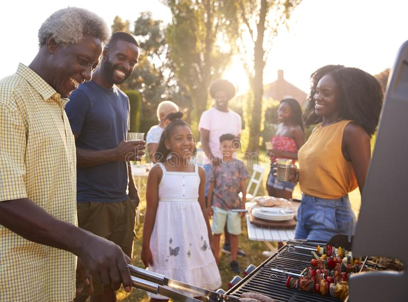 Multi generation black family barbecue, grandad grilling royalty free stock photo