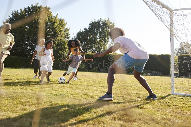 Multi generation black family playing football in a garden royalty free stock photos