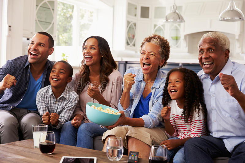 Multi generation black family watching sport on TV at home stock images