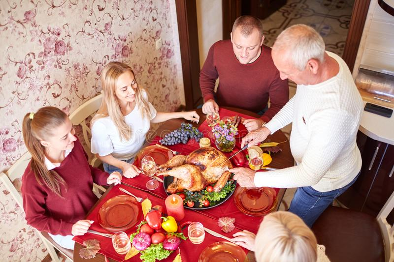 Happy family at the dinner table celebrating Thanksgiving on a blurred background. Traditional Thanksgiving concept. royalty free stock images