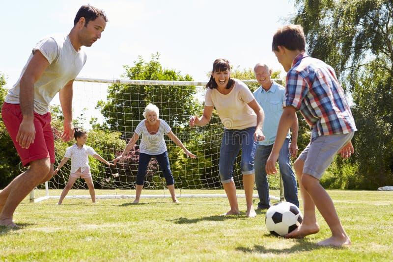 Multi Generation, die zusammen Fußball im Garten spielt lizenzfreie stockbilder