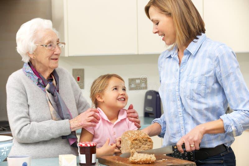 Multi-generation familj som förbereder mat i kök royaltyfria bilder