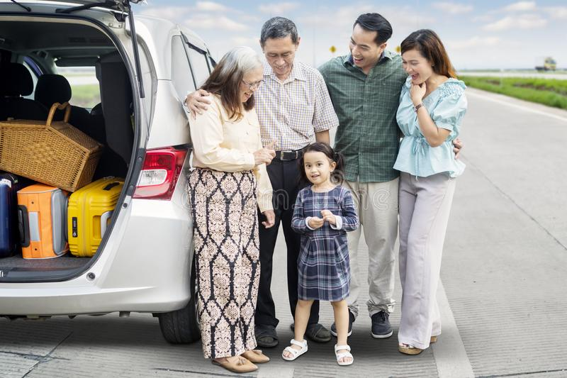 Multi generation family with car on the road stock photo