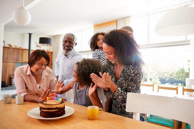 Multi-Generation Family Celebrating Granddaughters Birthday At Home With Cake And Candles stock photo