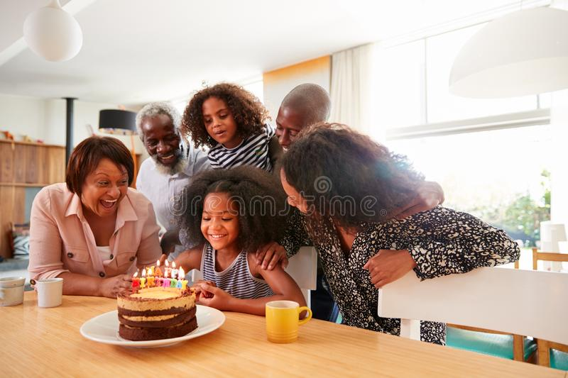 Multi-Generation Family Celebrating Granddaughters Birthday At Home With Cake And Candles stock images