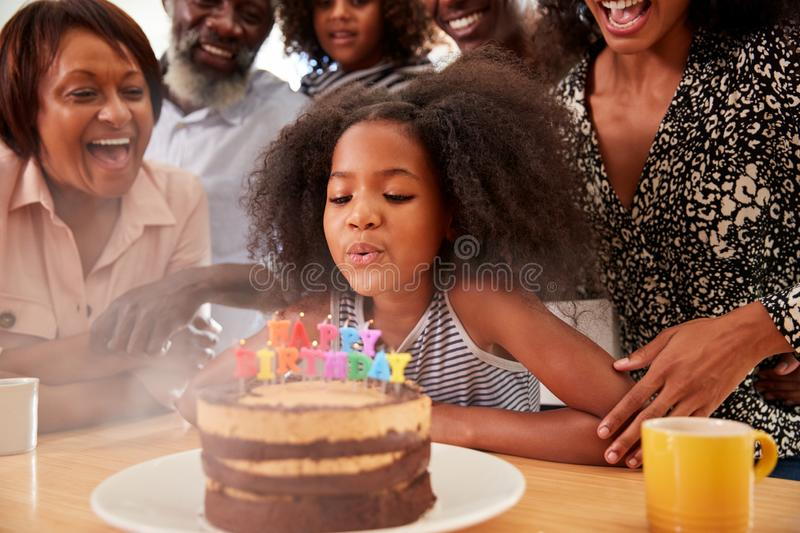 Multi-Generation Family Celebrating Granddaughters Birthday At Home With Cake And Candles royalty free stock images