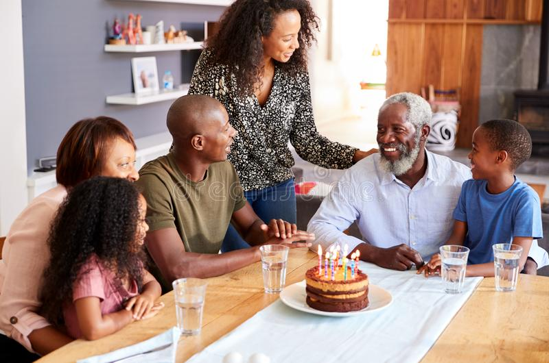 Multi-Generation Family Celebrating Grandfathers Birthday At Home With Cake And Candles royalty free stock photos
