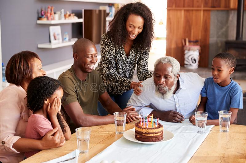 Multi-Generation Family Celebrating Grandfathers Birthday At Home With Cake And Candles stock photography