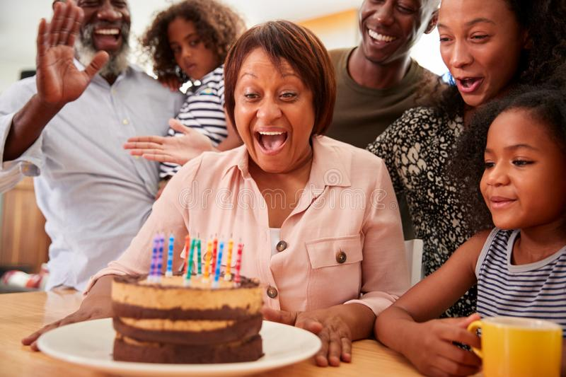 Multi-Generation Family Celebrating Grandmothers Birthday At Home With Cake And Candles royalty free stock images