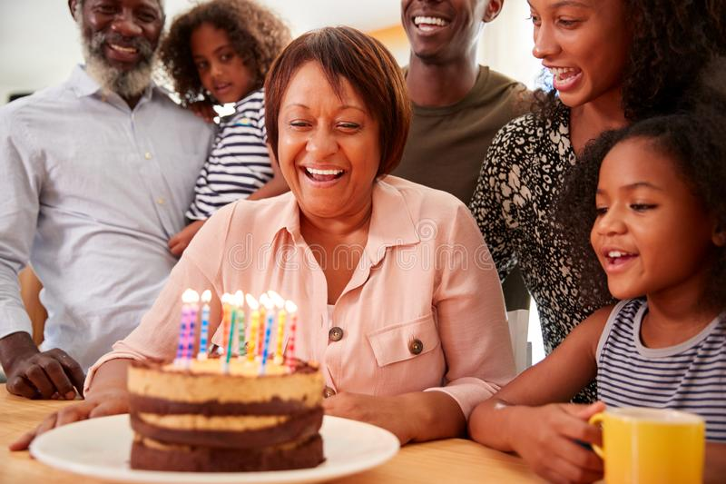 Multi-Generation Family Celebrating Grandmothers Birthday At Home With Cake And Candles royalty free stock image