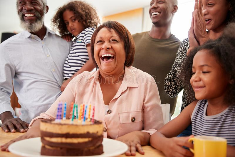 Multi-Generation Family Celebrating Grandmothers Birthday At Home With Cake And Candles stock photo