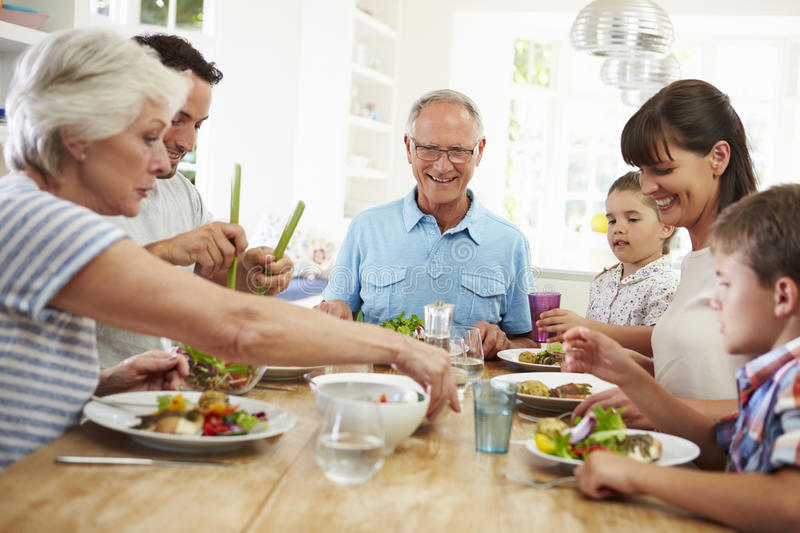 Multi Generation Family Eating Meal Around Kitchen Table royalty free stock images