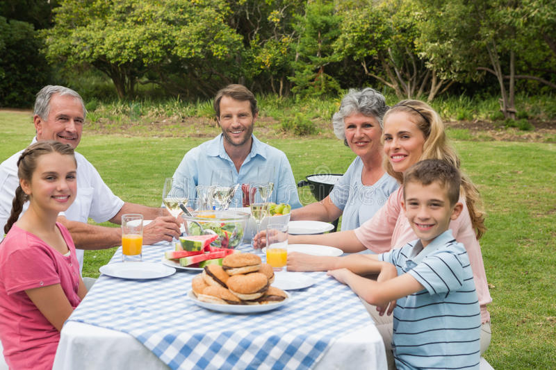 Multi generation family having dinner outside at picnic table. Smiling at the camera stock images