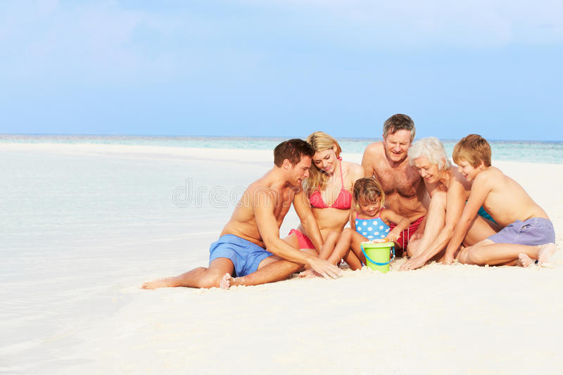 Multi Generation Family Having Fun On Beach Holiday. Playing stock photography