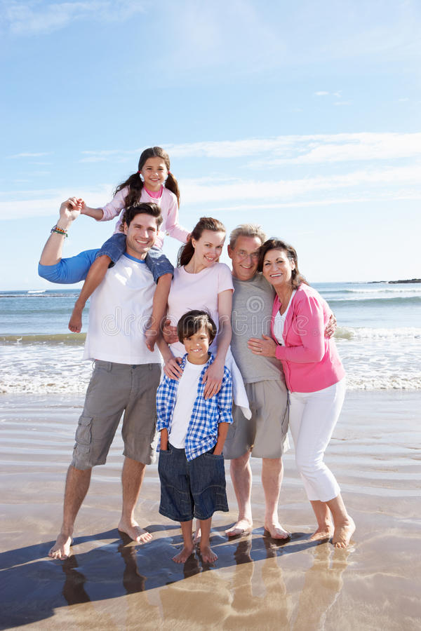 Multi Generation Family Having Fun On Beach Holiday. Smiling To Camera royalty free stock photography