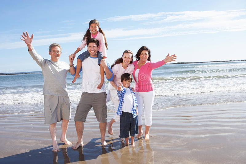 Multi Generation Family Having Fun On Beach Holiday. Smiling To Camera royalty free stock photos