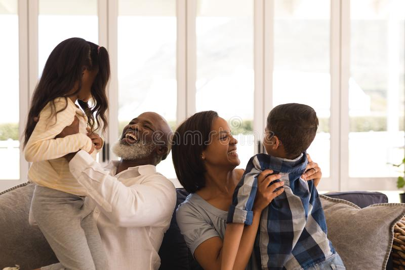Multi-generation family having fun in living room. Front view of a happy multi-generation African American family having fun in living room at home royalty free stock image