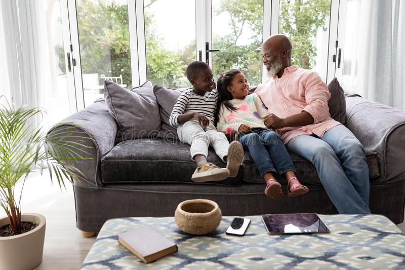 Multi-generation family having fun together on a sofa in living room. Front view of African american Multi-generation family having fun together on a sofa in stock photo